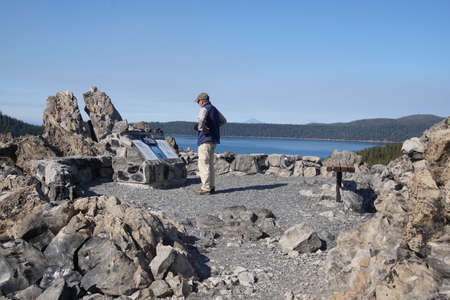 NEWBERRY CRATER, OREGON - OCT 22, 2018 - Tourist reading  information display in Big Obsidian Flow, Newberry National Volcanic Monument, Oregon Editorial