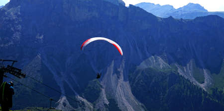 Parapentes launched from a high alpine meadow in the Dolomites Alps, Italy