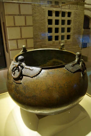ANKARA, TURKEY - MAY 21, 2014 -   Mythical winged figures on bronze cauldron, Gordion civilization from Kazan, 8th c BCE,  Museum of Anatolian Civilization,  Ankara, Turkey