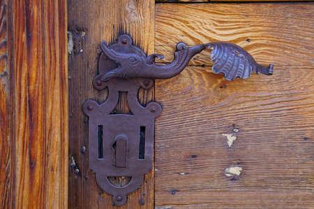 Antique fish door handle on old wooden door in Toblach, Italy