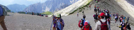DOLOMITES, ITALY - JUL 31, 2018 - Large group of hikers on the pass saddle under the Drei Zinnen area of the  Dolomites Alps, Italy Editorial