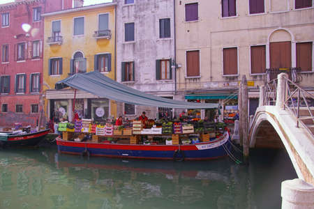 VENICE, ITALY - APR 16, 2018 - Vegetable boat delivers to small grocery store in Venice, Italy Editorial