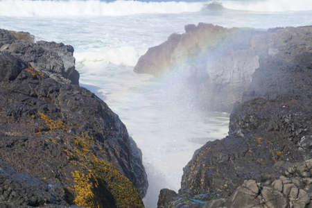 Misty rainbow forms at Thor's Well, Cape Perpetua, Oregon coast