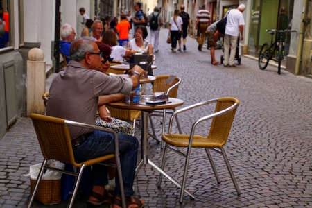 BOLZANO, ITALY - JUL 26, 2018 - People relax at outdoor cafe in old city of Bolzano, Italy 報道画像