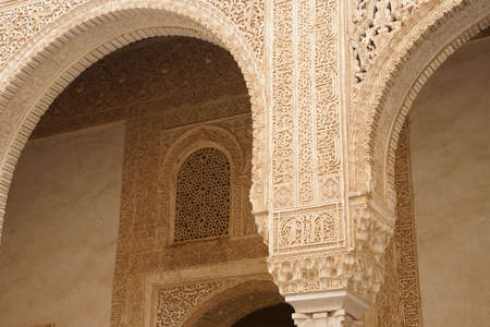 GRENADA, SPAIN - NOV 23, 2018 - Elaborate Islamic designed columns and arabesque window in the Alhambra Palace, Grenada, Spain