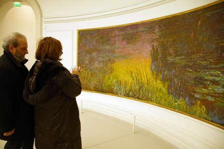 PARIS - Dezember 5, 2018 - Besucher sehen Monets riesige Seerosenöle im Museum L'Orangerie, Paris, Frankreich