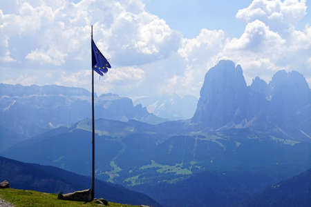 Tattered flag of the Euopean Union against the peaks of Langkofel in the Dolomites Alps, Italy