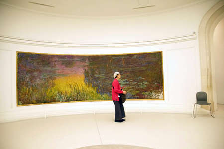 PARIS - DEC 5, 2018 - Visitors view Monets giant water lily oils in LOrangerie Museum, Paris, France