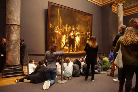 AMSTERDAM, NETHERLANDS - DEC 14, 2018 - School kids visit Rembrandt's Night Watch  in the Rijks Museum, Amsterdam, Netherlands 에디토리얼