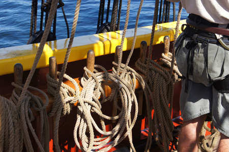 Coiled rope lines stored on belaying pins  on a wooden tall ship near Kirkland , Washington.