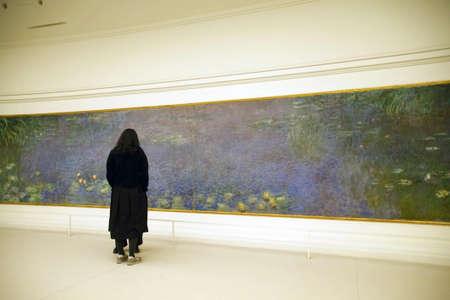 PARIS - DEC 5, 2018 - Visitors view Monets giant water lily oils in LOrangerie Museum, Paris, France