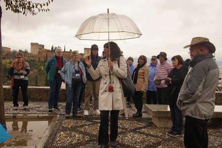 GRENADA, SPAIN - NOV 23, 2018 - Tour guide describes the Alhambra for her group in Grenada, Spain 新聞圖片