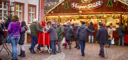 HEIDELBERG, GERMANY - DEC 19, 2018 - Visitors drink gluwein on a winter afternoon at the Christmas market,Heidelberg, Germany Stock Photo - 115463583