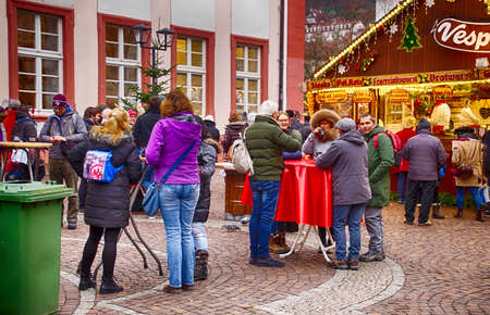 HEIDELBERG, GERMANY - DEC 19, 2018 - Visitors drink gluwein on a winter afternoon at the Christmas market,Heidelberg, Germany Editorial