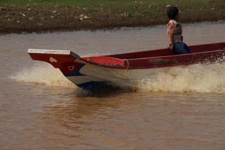 KOMPONG KLEANG, CAMBODIA - FEB 12, 2015 - Power boat travels along the waterway of Kompong Kleang floating fishing village,  Cambodia