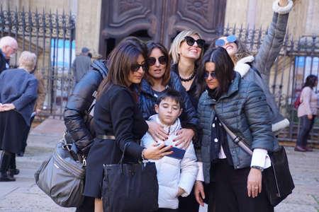MALAGA, ESPAGNE - 24 NOVEMBRE 2018 - Jeune garçon prenant selfie avec ses parents féminins devant la cathédrale de Malaga, Espagne