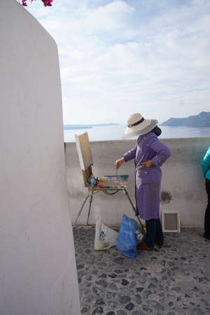 Woman painting  with oils in Santorini, Greece Редакционное