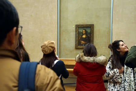 PARIS - DEC 6, 2018 - Visitors view and photograph the Mona Lisa in the Museum de Louvre, Paris, France