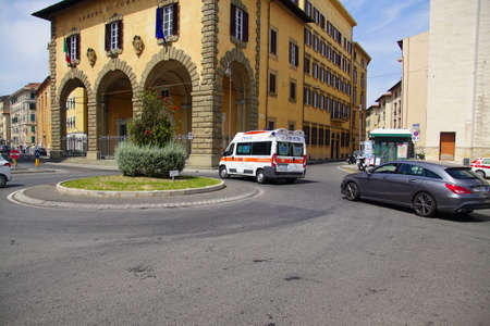 LIVORNO, ITALY - APR 23, 2018 - Ambulance on the roundabouit in front of the Loggia of the Chamber of  Commerce, Livorno, Italy