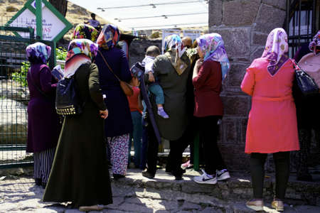 ASSOS, TURKEY - MAY 1, 2018 - Local villagers wait at the entrance to the temple ruins at Behramkale Assos, Turkey