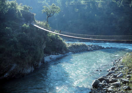 Porters carrying loads across suspension bridge over river,Arun Valley,  Himalayas, Nepal, Asia