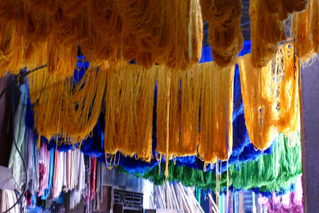 Dyed yarn skeins hanging to dry in the medina bazaar of Marrakech,  Morocco