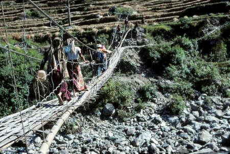 Hiker crossing suspension bridge over river,Kangchenjunga Himalayas, Asia