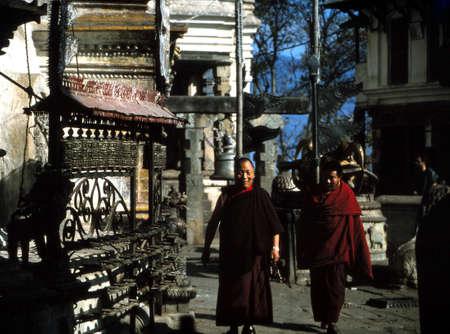 KATHMANDU, NEPAL - DEC 14, 1977 - Buddhist monks and prayer wheels at Swyambudnath Temple, Kathmandu, Nepal Redactioneel