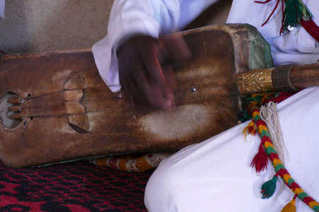 Ethnic Gnawa tribesman playing traditional string instrument,   Rissani, Morocco, Africa Standard-Bild - 118380481