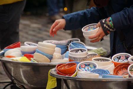 Selecting small porcelain bowls in Chritmas market of Heidelberg, Germany Фото со стока