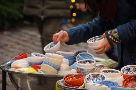 Selecting small porcelain bowls in Chritmas market of Heidelberg, Germany Stock Photo