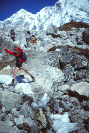 LANGTANG, NEPAL - OCT 25, 1986 - Hiker crossing a mountain stream in the Lantang Himal, Nepal, Asia Editorial