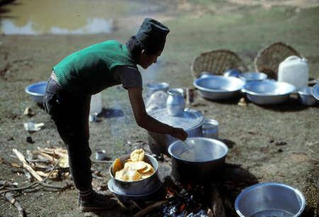 LANGTANG, NEPAL - OCT 15, 1986 - Kitchen boy cooking puri breads over firewood in the Helambu Himalayas,Nepal, Asia