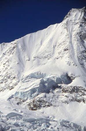 Hanging glacier on steep mountain peak near Saas Fee, Swiss alps Stock Photo