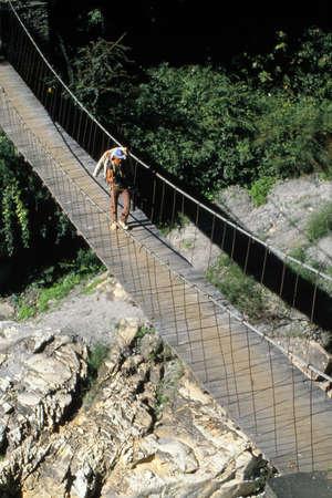 Crossing a suspension bridge over the Kali Gandaki river, Himalaya,Nepal 版權商用圖片
