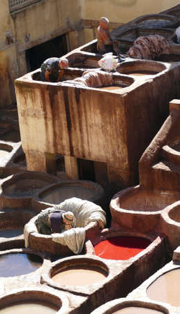 FES, MOROCCO - FEB 13, 2019 - Workers prepare hides in pits of the leather tannery of medina of Fes, Morocco, Africa