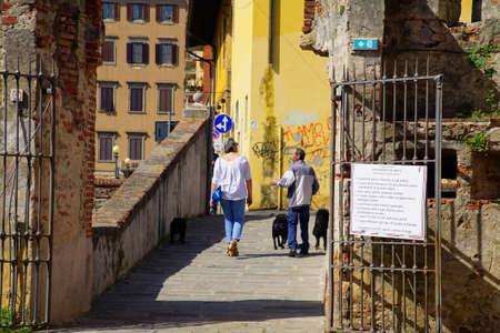 LIVORNO, ITALY - APR 23, 2018 - Dog walkers chat while walking near Fortezza Nuova, Livorno, Italy Editorial