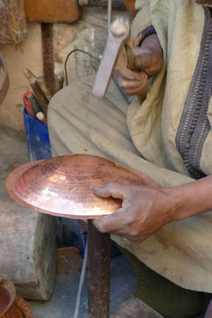 Metalworker uses ball peen hammer to form copper dish in the medina of Fes, Morocco, Africa