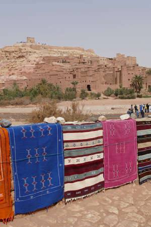 Bright colored carpets frame the hilltop village of Ait ben Haddou, Morocco, Africa Stockfoto