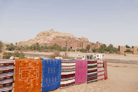 Bright colored carpets frame the hilltop village of Ait ben Haddou,  Morocco, Africa Standard-Bild - 120704745