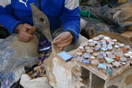 Using hammer to shape mosaic tile pieces, Artisanal pottery workshop, Fes, Morocco, Africa