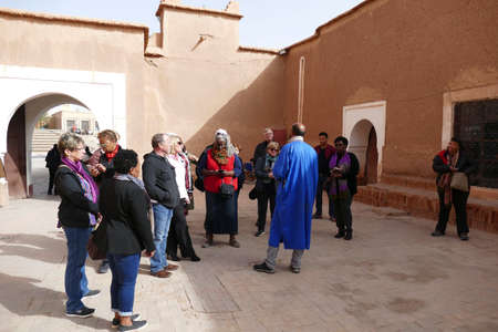 OUARZAZATE, MOROCCO - FEB 17, 2019 - Mohammed the guide leads his tour group in the Kasbah Taourirt, Ouarzazate,  Morocco, Africa Standard-Bild - 120755077