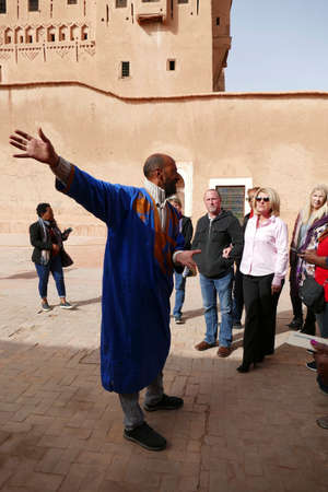 OUARZAZATE, MOROCCO - FEB 17, 2019 - Mohammed the guide leads his tour group in the Kasbah Taourirt, Ouarzazate,  Morocco, Africa Standard-Bild - 120915118