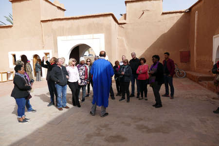 OUARZAZATE, MOROCCO - FEB 17, 2019 - Mohammed the guide leads his tour group in the Kasbah Taourirt, Ouarzazate,  Morocco, Africa Standard-Bild - 120915124