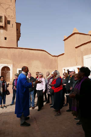 OUARZAZATE, MOROCCO - FEB 17, 2019 - Mohammed the guide leads his tour group in the Kasbah Taourirt, Ouarzazate,  Morocco, Africa Standard-Bild - 120915113