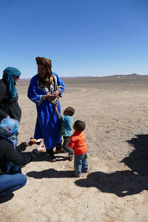 MERZOUGA, MOROCCO - FEB 15, 2019 - Tuareg nomad children greet a visitor  in the Sahara Desert near Merzouga, Morocco, Africa