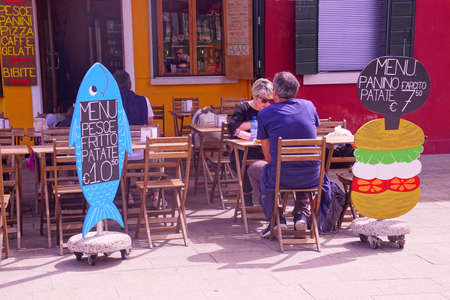 BURANO, ITALY - APR 16, 2018 - Whimsical placards in an outdoor café on Burano Venice, Italy Editorial