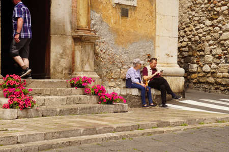 TAORMINA, ITALY- APR 18, 2018 - Tourists rest on stone steps in Taormina Sicily, Italy Editorial
