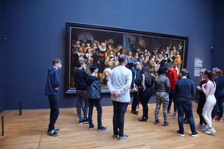 AMSTERDAM, NETHERLANDS - DEC 14, 2018 - Visitors view famous paintings in the Rijks Museum, Amsterdam, Netherlands