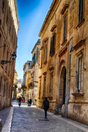 LECCE, ITALY - APR 6, 2019 - Narrow street with limestone buildings in Lecce, Puglia, Italy
